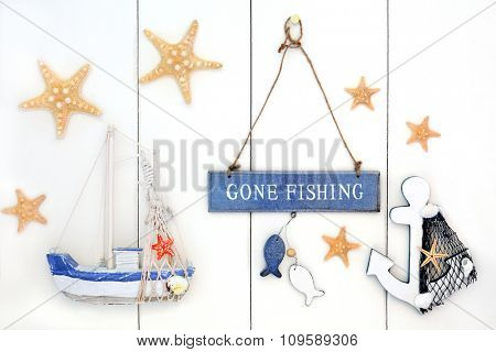 Abstract background with gone fishing sign, starfish, decorative anchor and boat over white wood.