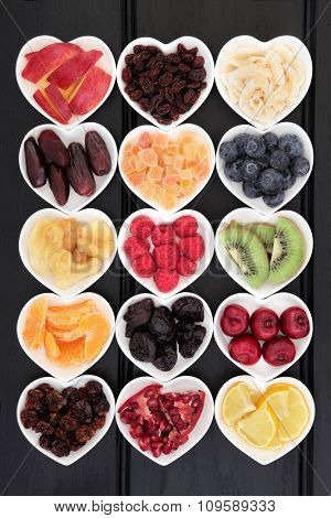 Dried and fresh mixed fruit superfood selection in heart shaped bowls over wooden black background.