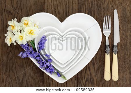 Floral table place setting with white heart shaped porcelain bowls, bluebell and narcissus flowers with antique cutlery over old rustic oak background.