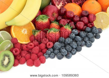 Fresh mixed fruit superfood background selection with fruits high in antioxidants, vitamin c and dietary fibre with copy space.