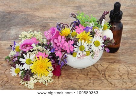 Natural herbal medicine with flower and herb selection in a mortar and  pestle with dropper bottle over distressed wooden background.