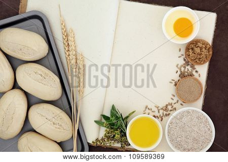 Fresh dough bread rolls with baking ingredients, wheat sheaths and herbs on old hemp notebook over lokta background.