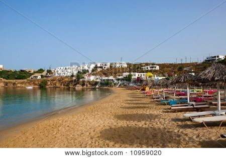 Sandy Beach On The Island Of Mykonos With Umbrellas And Color Sun Beds