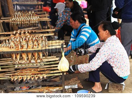 Asian women roasting caught fishes