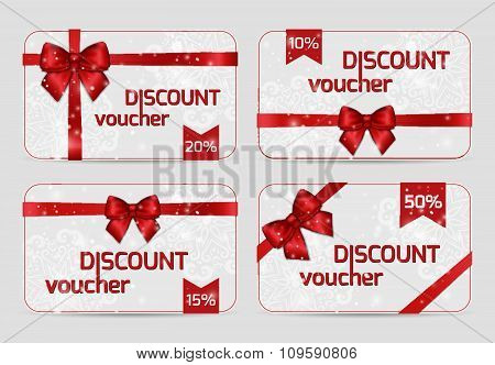 Set Of Ornamental Discount Voucher Cards With Shiny Holiday Red Satin Ribbon Bow On White Lacy Backg