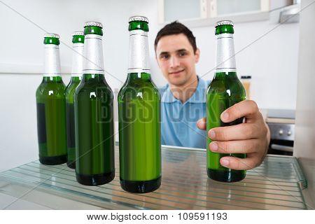 Smiling Man Removing Beer Bottle From Refrigerator