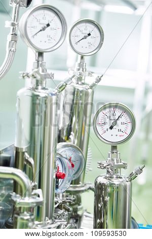 Closeup of manometer, pipes and faucet valves of heating system in a boiler room on pharmaceutical factory
