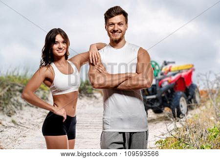 Young And Beautiful Athletic Woman And Man Posing Outdoors