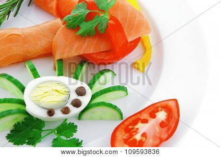 diet healthy food - fresh smoked sea salmon rolls with tomatoes egg and resemary on plate isolated over white background