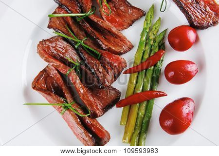 grilled red beef meat rolls with asparagus and hot spices on china plate isolated over white background