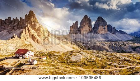 Great sunny view of the National Park Tre Cime di Lavaredo with rifugio Locatelli. Dolomites, South Tyrol. Location Auronzo, Italy, Europe. Dramatic cloudy sky. Beauty world.