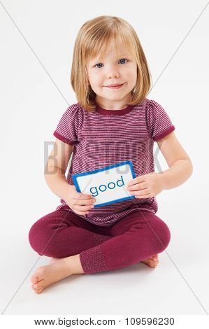 Young Girl In Studio Learning To Read Using Flash Card