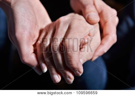 Young Woman Holding Old Woman's Hand Against Black Background