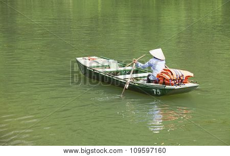 Vietnamese woman with conical hat paddling her boat