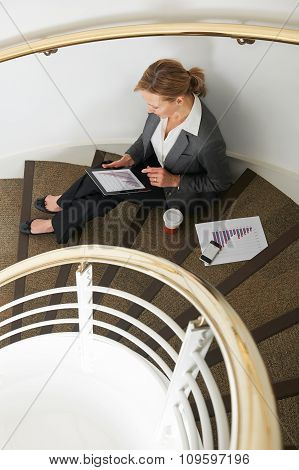 Businesswoamn Using Tablet Computer Sitting On Stairs