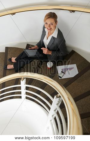 Businesswoman Sitting On Stairs Preparing For Meeting With Digit
