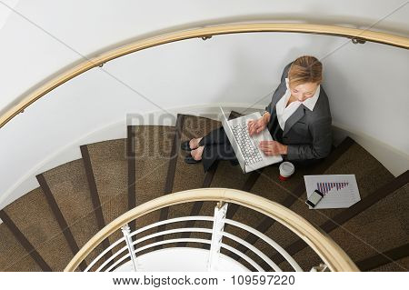 Businesswoman Sitting On Stairs Using Laptop