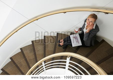 Businesswoman Sitting On Stairs On Mobile Phone