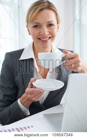 Businesswoman Working At Desk With Hot Drink