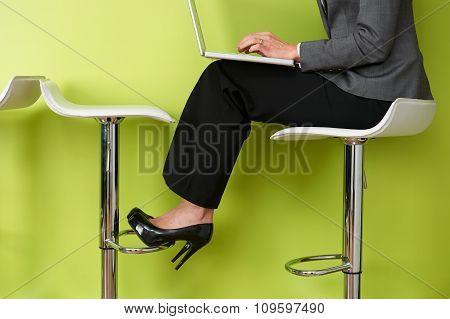 Close Up Of Businesswoman Sitting On Stool Using Laptop