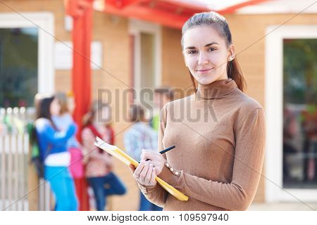 Portrait Of Teacher In Playground With Register