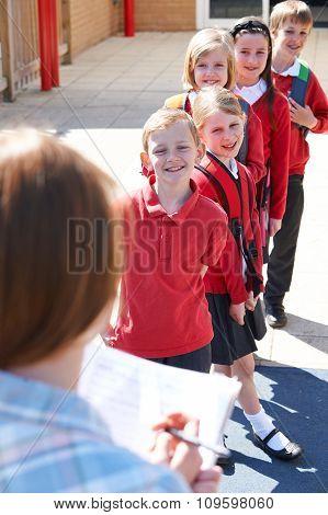 Teacher Taking School Register In Playground