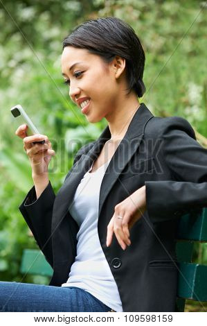 Young Woman Sitting On Bench Reading Text Message