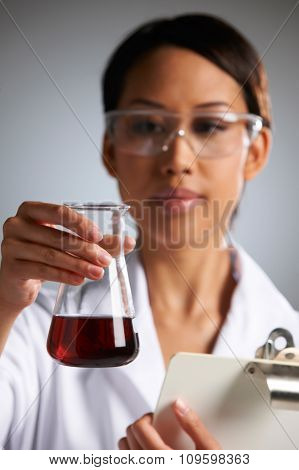 Scientist Examining Liquid In Flask Holding Clipboard