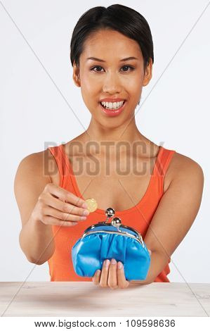 Smiling Woman Putting Coin In Purse