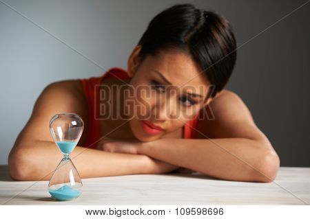 Sad Woman Looking At Hourglass