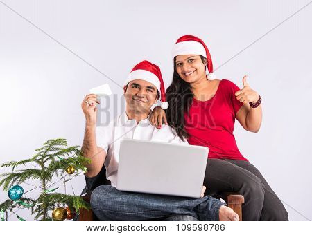 young indian couple with red santa hat, sitting close on couch with christmas tree, white card in ha