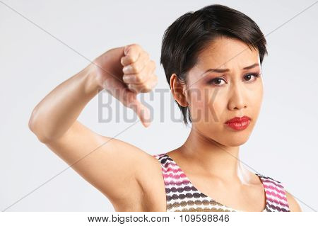 Studio Shot Of Woman Giving Thumbs Down Gesture