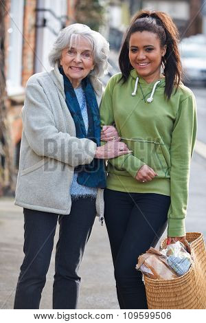 Teenage Girl Helping Senior Woman Carry Shopping