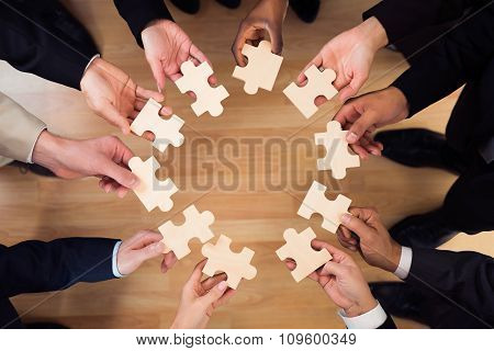 Business People Joining Puzzle Pieces In Office