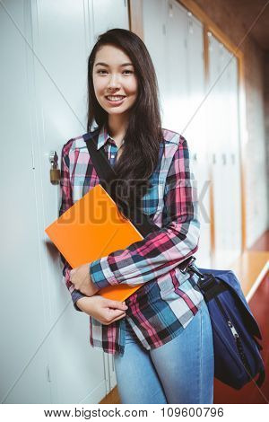 Cheerful student standing next the locker at the university