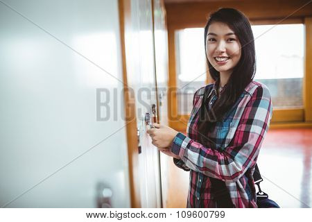 Smiling student opening locker at the university