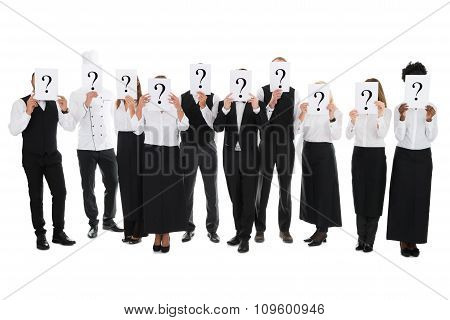Restaurant Staff Hiding Faces With Question Mark Signs