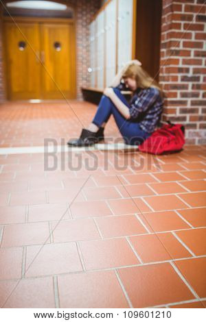 Thoughtful student sitting on the floor against the wall at the university