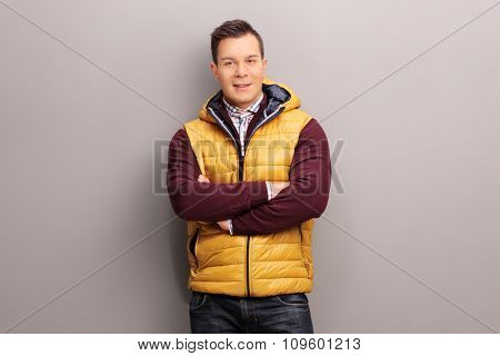 Cheerful young man in casual clothes leaning against a gray wall and looking at the camera