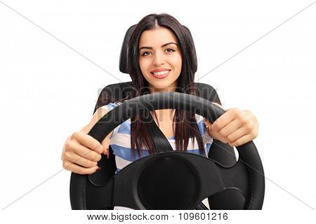 Young girl holding a steering wheel and pretending to drive seated on a car seat isolated on white background