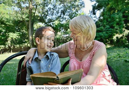 Laughing Boy And His Grandmother Reading A Book In The Park