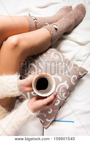 Beautiful young woman sitting in bed with cup of coffee