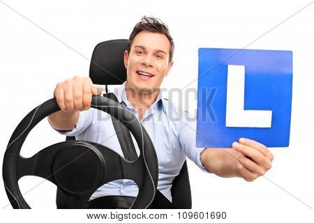 Young man pretending to drive seated on a car seat and holding an L-sign isolated on white background