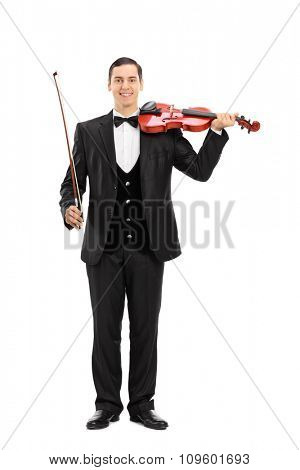 Full length portrait of an elegant young musician holding a violin and looking at the camera isolated on white background
