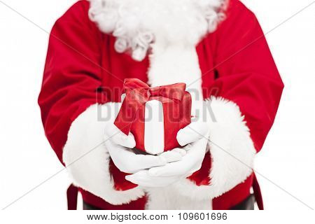 Close-up on Santa Claus holding a present wrapped with a red ribbon isolated on white background with the focus on the present