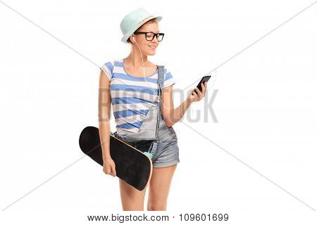 Studio shot of a hipster girl holding a skateboard and listening music on her cell phone isolated on white background