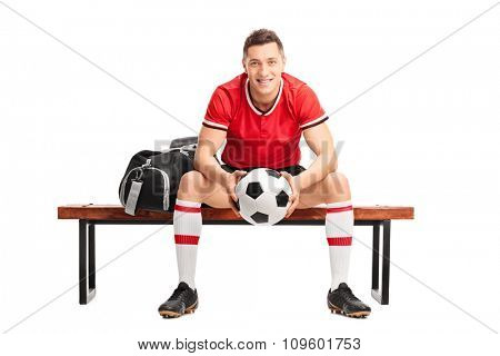 Young football player holding a ball and sitting on a wooden bench isolated on white background