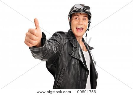 Joyful young biker with black leather jacket giving a thumb up and looking at the camera isolated on white background