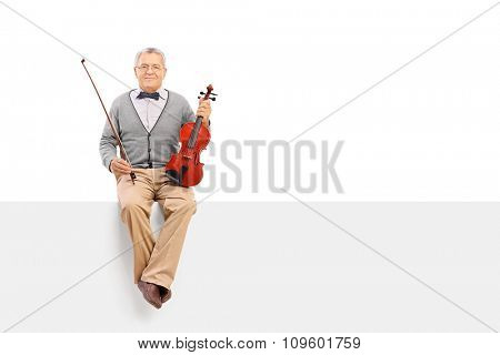 Mature violinist holding an acoustic violin and sitting on a blank signboard isolated on white background