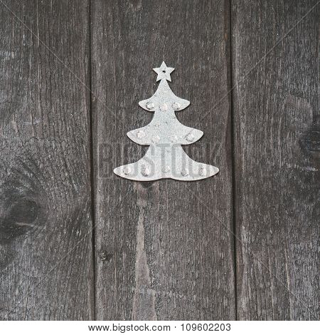 Silver Christmas decoration on wooden vintage background. Little silver Christmas tree